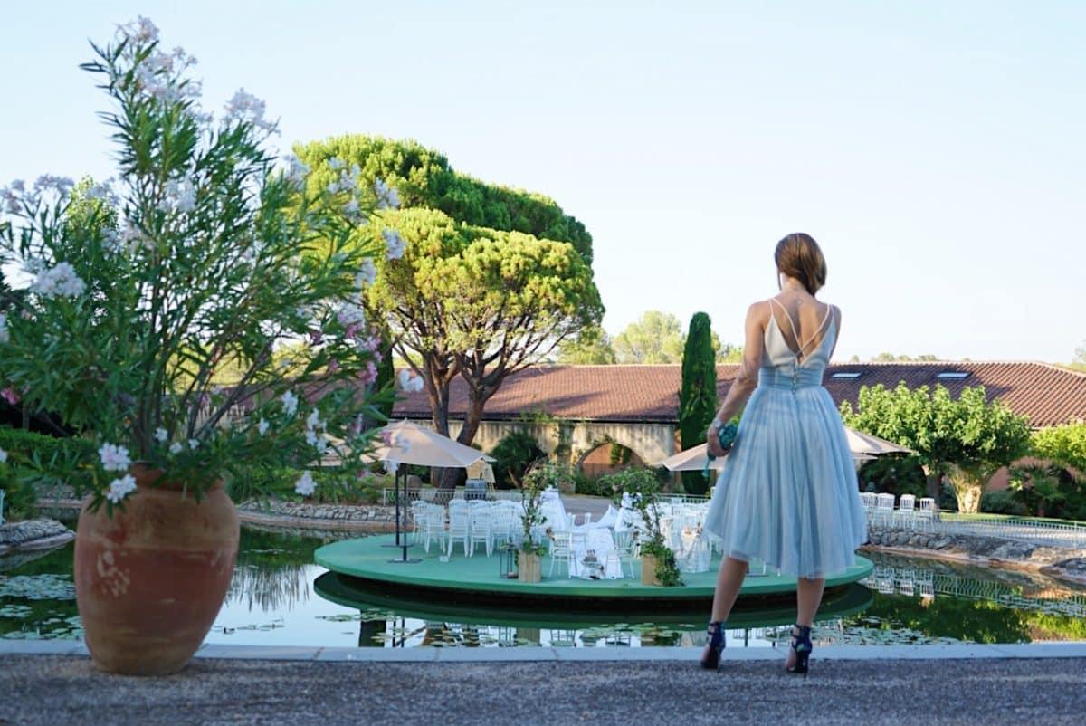 Une demoiselle vêtue de sa robe d'invitée à un mariage dans un jardin